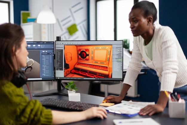스튜디오 사무실의 프로젝트에서 함께 작업하는 듀얼 디스플레이가 있는 컴퓨터를 보고 있는 다민족 여성 게임 디자이너