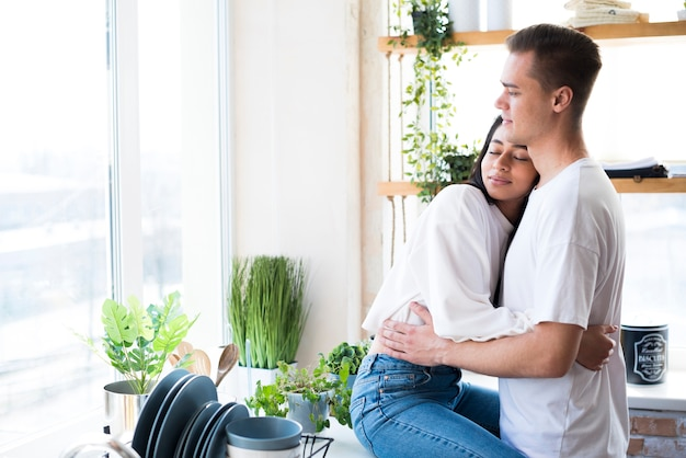 Multiethnic young couple in love hugging in kitchen