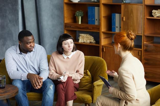 ソファに座って、オフィスで心理学者の話を聞いている多民族の若いカップル