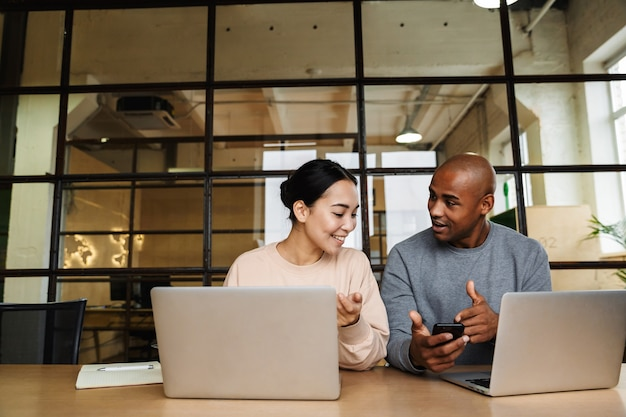 다민족 젊은 여성 및 남성 동료들이 책상에 앉아 사무실에서 노트북 작업을 하고 있다