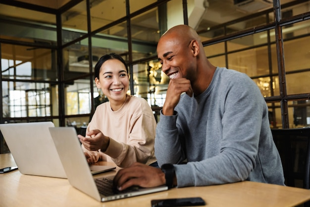 Multiethnic young female and male coworkers sitting at table and working on laptops in office