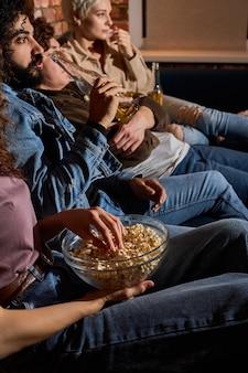 Молодые многонациональные друзья вместе смотрят фильм дома ночью, едят закуски из попкорна, фото крупным планом, сосредотачиваются на попкорне, одеваются небрежно, проводят вместе выходные