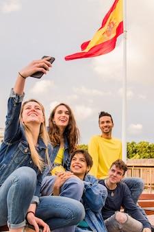Многонациональная молодая группа из разных этнических групп делает селфи на мобильный телефон в испании