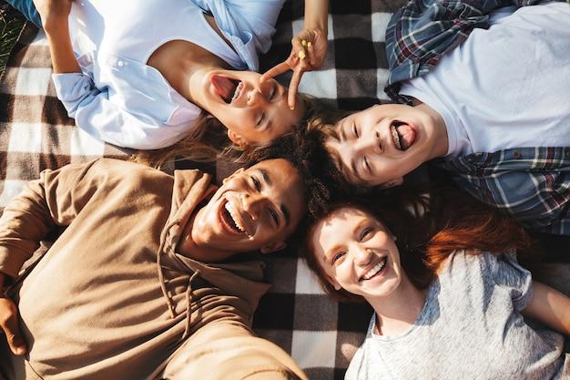 다민족 젊은이들과 소녀들은 웃고 야외에서 담요에 누워 있습니다.