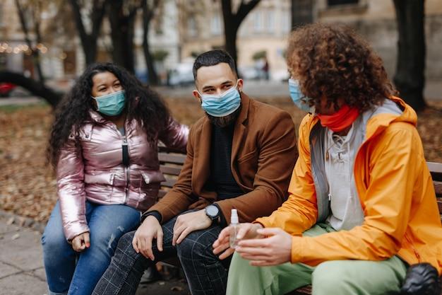都市公園の木製ベンチに座って、コロナウイルスから保護するために医療用マスクを着用している多民族の若者。感染症の概念。