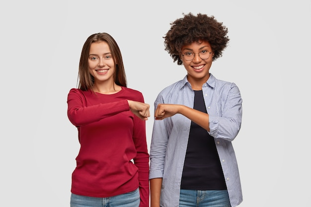 多民族の若い女性はお互いに拳バンプを与えます