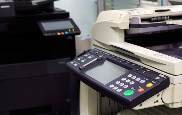Multifunction printer in office with soft-focus and over light in the background
