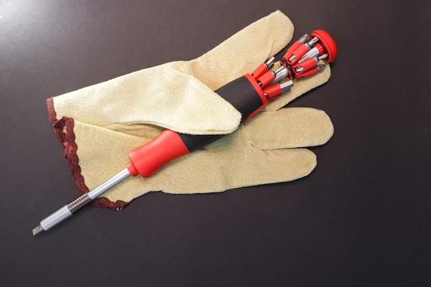 건설 장갑에서 다양한 유형의 작업을 위해 교체 가능한 비트가 있는 다기능 스크루드라이버. 건설 및 수리. 손 도구입니다. 보호 수단.
