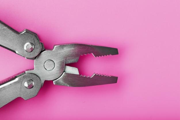 분홍색 배경에 다기능 도구 근접입니다. 여유 공간이있는 포켓 도구의 개념.