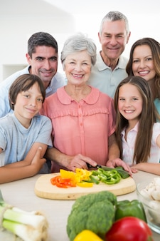 Multigeneration family preparing food at counter