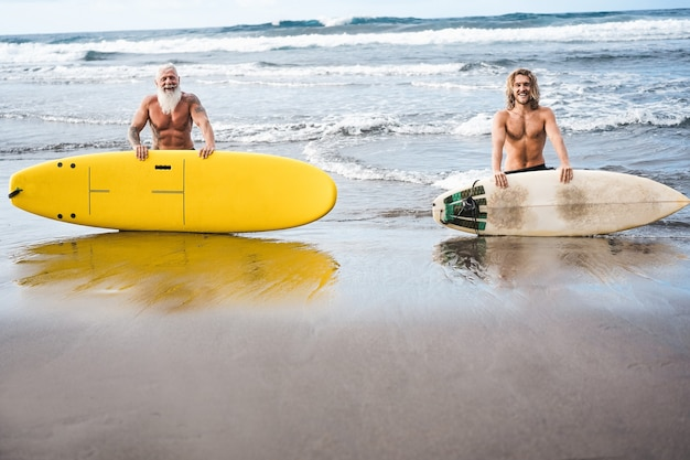 Multigeneration friends going to surf on tropical beach - family people having fun doing extreme sport - joyful elderly and healthy lifestyle concept - main focus on faces