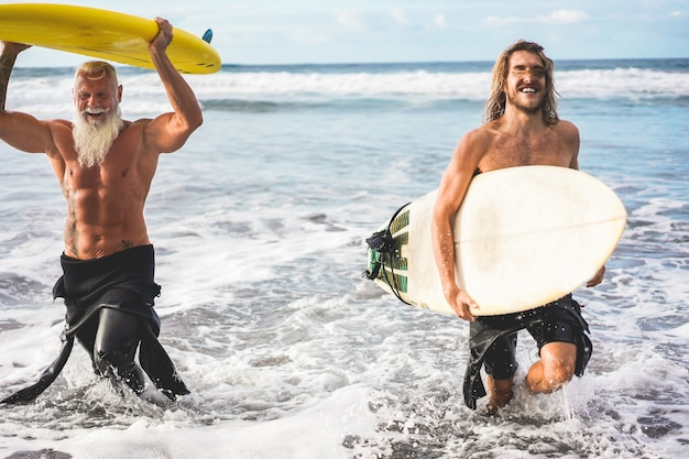 Multigeneration friends going to surf on tropical beach - family people having fun doing extreme sport - joyful elderly and healthy lifestyle concept - main focus on senior face