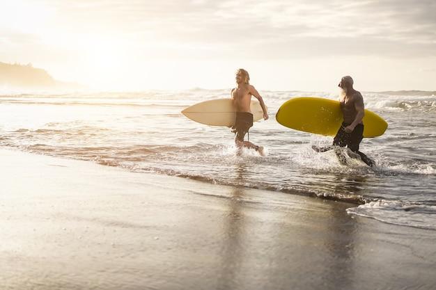 島のビーチでサーフボードを持ってビーチに沿って走っている多世代の友人-顔に焦点を当てる