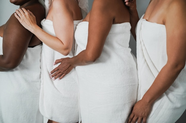 다양한 피부와 몸을 가진 다세대 여성, 바디 타월을 끼고 함께 즐겁게 노는 여성 - 왼손을 중심으로