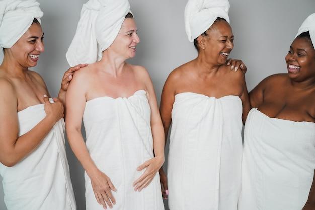 다양한 피부와 몸을 가진 다세대 여성, 바디 타월을 착용하면서 함께 즐겁게 노는 여성 - 왼쪽 여성의 얼굴에 부드러운 초점
