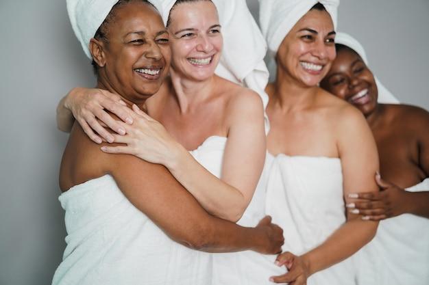 다양한 피부와 몸을 가진 다세대 여성들이 바디 타월을 입고 함께 웃고 - 아프리카 여성의 얼굴에 초점