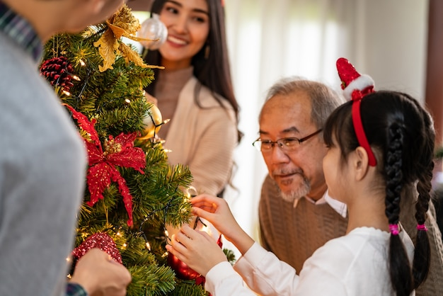 クリスマスツリーを飾る多世代のアジアの家族