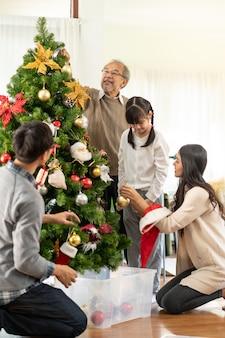 Multigenerational asian family decorating a christmas tree.