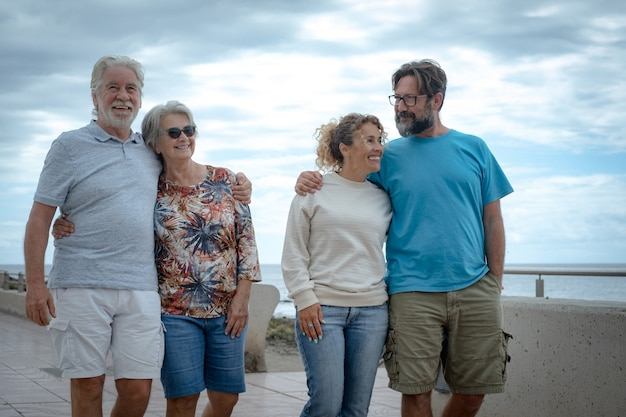 Multigenerational family group strolls outdoors by the sea, hugging each other and smiling. horizon over the water and cloudy sky