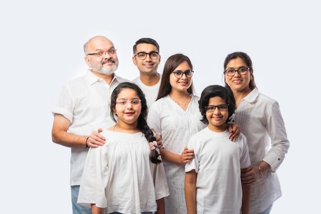 多世代のインドのアジアのスマートな家族は、白い背景に対して透明な眼鏡または眼鏡または眼鏡をかけています