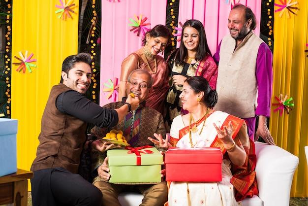 Индийская семья из нескольких поколений ест сладости во время праздника или праздника, одетая в традиционную одежду, сидя на диване или диване