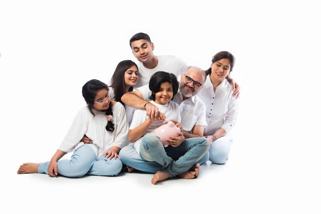 白い布を着て白い壁に立っている間貯金箱を保持している6人の多世代のインドの家族