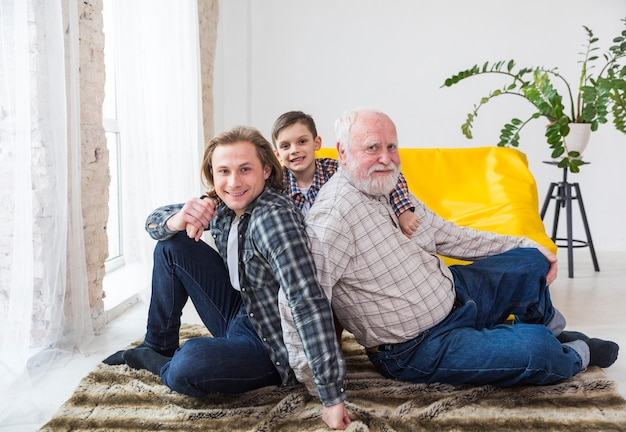 Multigenerational men sitting on carpet at home