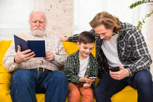 Multigenerational men spending time together browsing book and smartphones