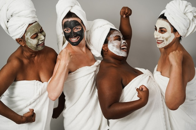 フェイスビューティーマスクを身に着けて楽しんでいる多世代の女性-スキンケア療法と女性の力-白人女性の顔に主な焦点