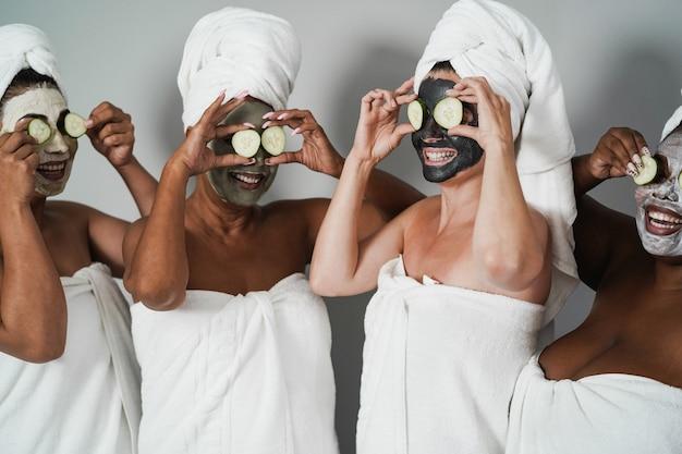 キュウリを目にしたフェイスビューティーマスクを楽しんでいる多世代の女性-スキンケア療法-白人女性の顔に主な焦点