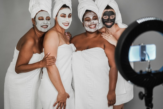 Multigenerational women wearing face beauty masks while streaming online video with mobile phone -