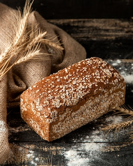 Multigrain bread with wheat and flour on table