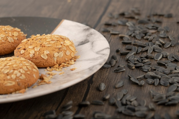 검은 해바라기 씨를 가진 multigrain 쿠키는 나무 테이블에 배치합니다.
