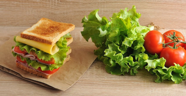 Multilayered sandwich with cheese, ham, tomatoes and lettuce