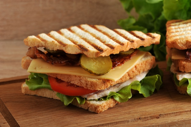 Multilayered sandwich with cheese, ham, tomatoes, pickles and lettuce photographed closeup