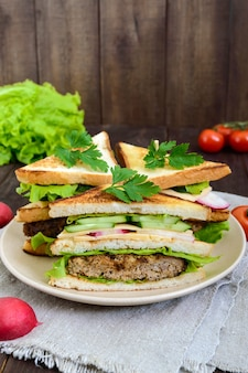 Multilayered sandwiches with a juicy cutlet, cheese, radish, cucumber, lettuce, arugula cutting in half on a plate on a dark wooden background. vertical view