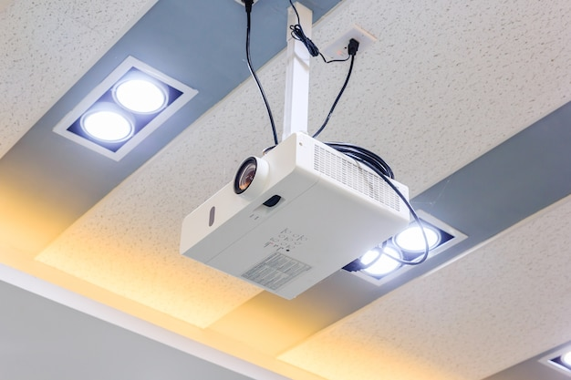 Multimedia projector hanging on the ceiling of modern conference room.