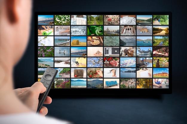 Человек концепции потоковой передачи мультимедиа держит пульт дистанционного управления