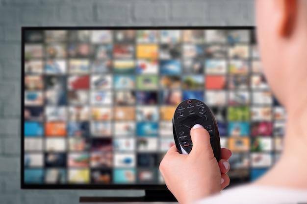 マルチメディアストリーミングの概念。女性はリモートコントロールを保持しています。写真の多いテレビ画面。 vodコンテンツプロバイダーの概念