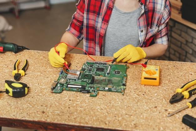 Мультиметр для электрика. крупным планом женщины в желтых перчатках, очки цифровой ремонт инженер-электронщик, пайка материнской платы пк компьютера в мастерской за деревянным столом с различными инструментами.
