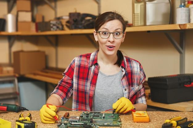 Мультиметр для электрика. довольно молодая женщина в желтых перчатках, очках, ремонт цифровых электронных инженеров, пайка материнской платы пк компьютера в мастерской за деревянным столом с различными инструментами.