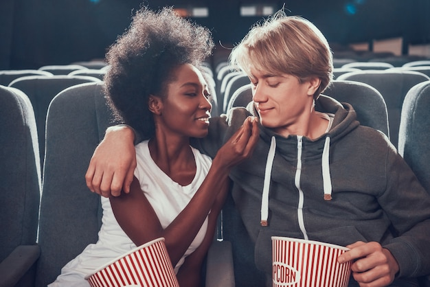 Multinational couple is feeding each other in cinema.