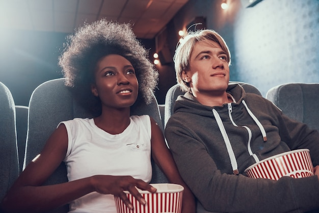 Multinational couple with popcorn sits in movie theater