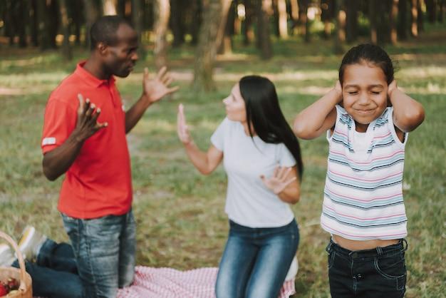 Multinational family picnic quarrel. sad child.