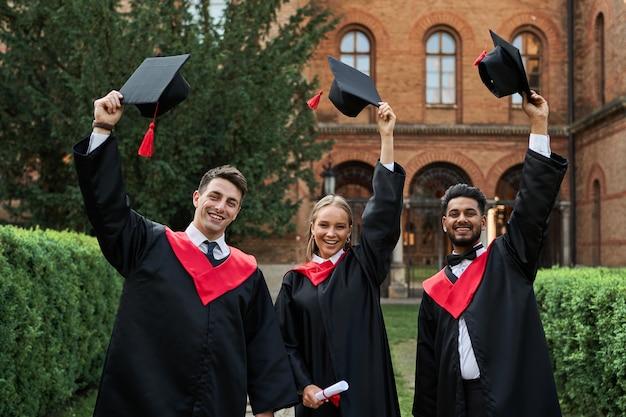 Laureati multinazionali maschi e femmine che celebrano la laurea nel campus universitario, togliendosi i cappelli di laurea e sorridendo alla telecamera.