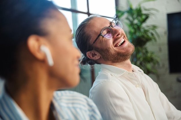 Multinational joyful colleagues with earphones talking and laughing while working in office