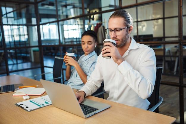 ラップトップで作業し、オフィスのテーブルに座ってコーヒーを飲む多国籍の真面目な同僚