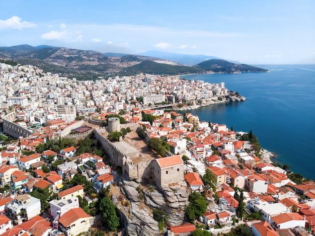 ギリシャ、カバラの背景にある複数の建物と砦、緑の丘