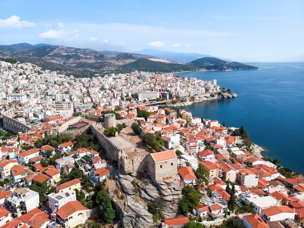 Multiple buildings and fort, green hills on the background in kavala, greece