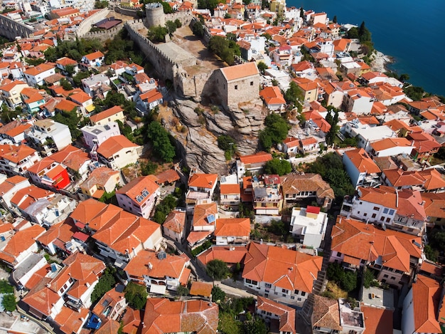 Multiple buildings with orange roofs and fort, kavala, greece